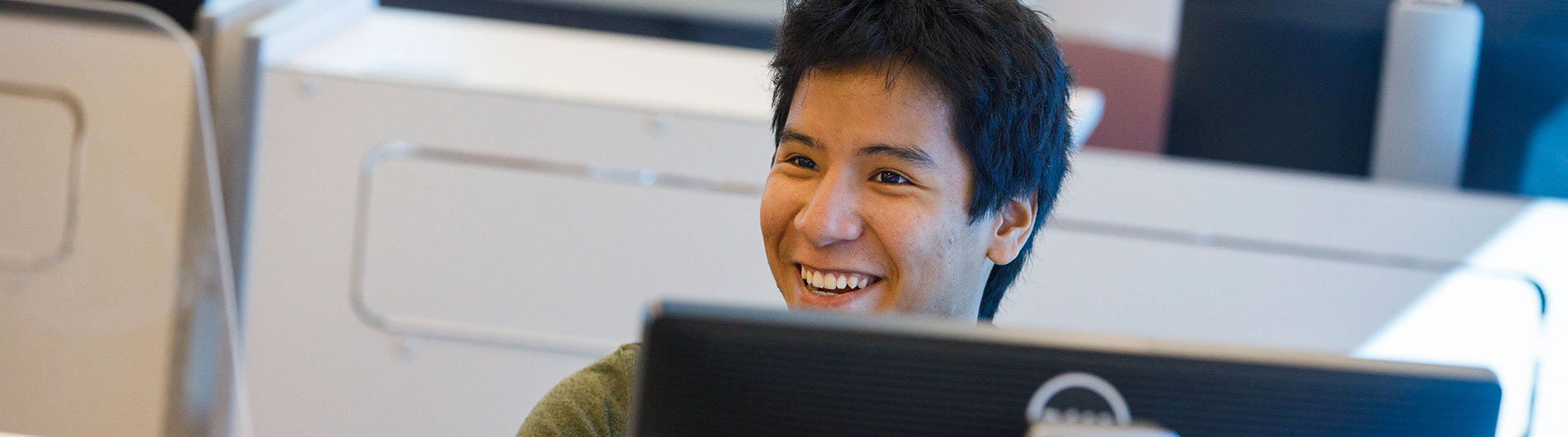 Male student in computer lab smiling and talking with counselor or adviser