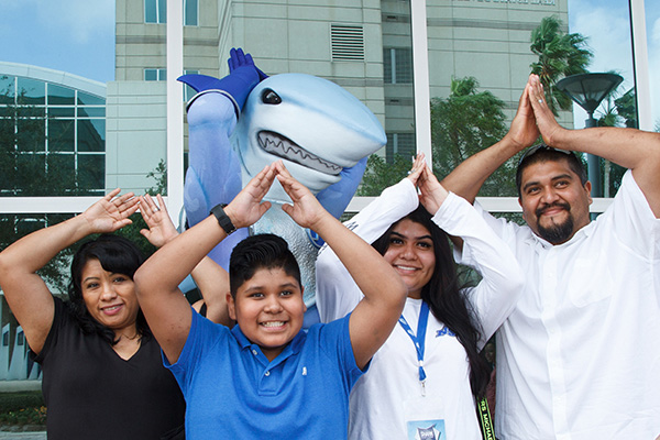 Happy family doing the NSU Florida Fins Up! pose at Shark Preview Weekend