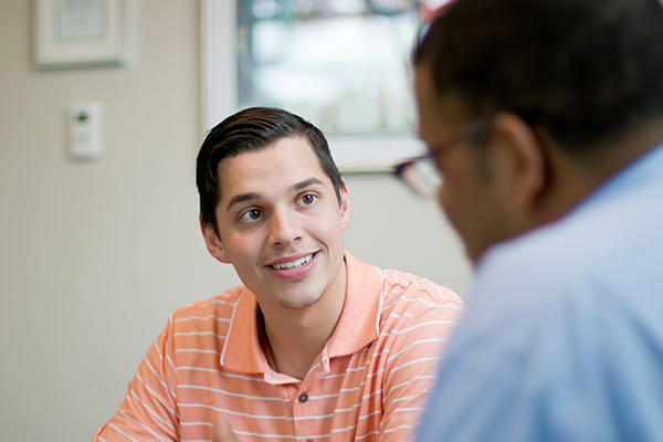 Male student in an orange shirt speaking with a counselor or adviser