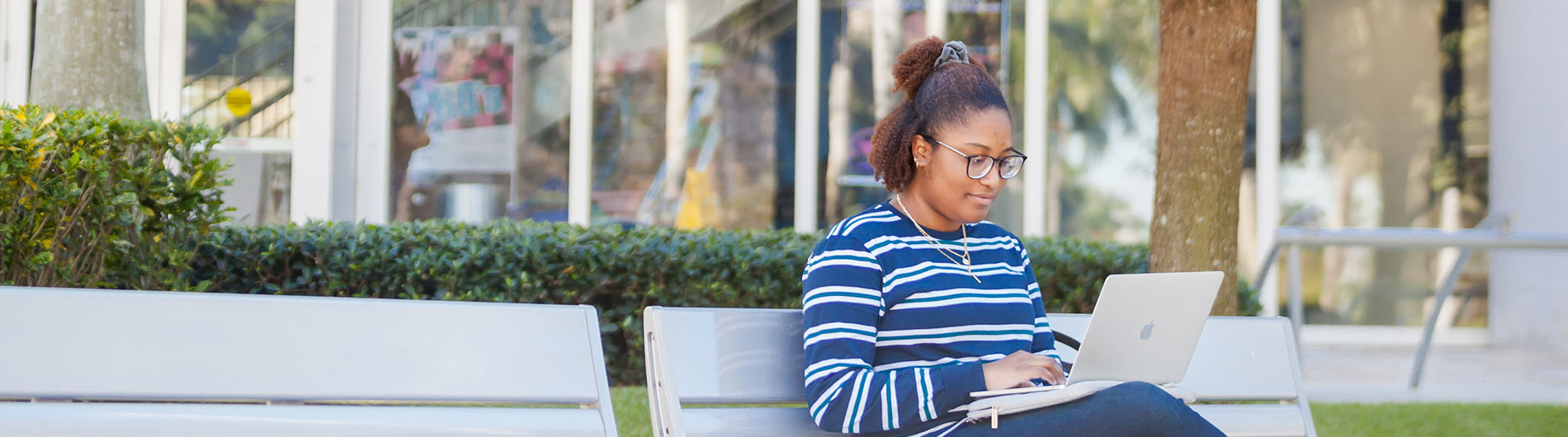 Female student working on a laptop on a bench outside and talking outside